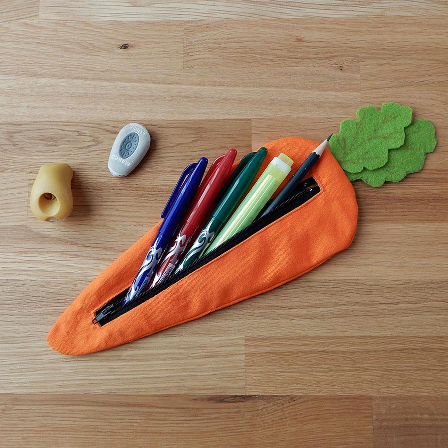 trousse carotte rempli de stylos avec une gomme et un taille-crayon